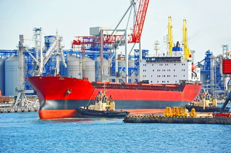 Tugboat assisting bulk cargo ship to harbor quayside Stock Photo