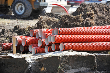 Stacked new PVC pipe on construction site