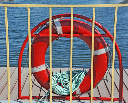 Red lifebuoy with rope on metal fence