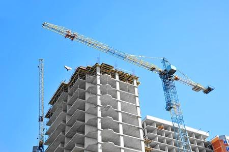social apartment: Crane and building under construction against blue sky Stock Photo