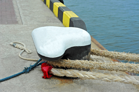Old mooring bollard with rope in port Stock Photo