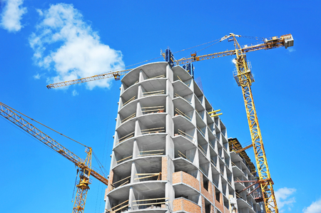 dwelling: Crane and building under construction against blue sky Stock Photo