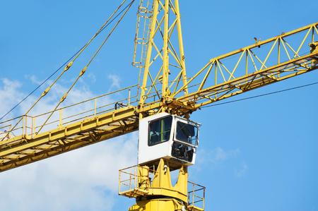 Tall construction tower crane against blue sky