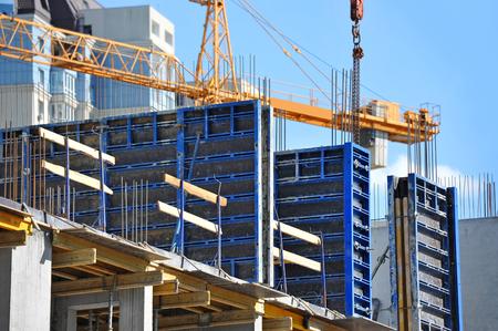 Kraan en gebouw in aanbouw tegen de blauwe hemel