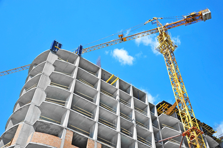 residential construction: Crane and building under construction against blue sky Stock Photo