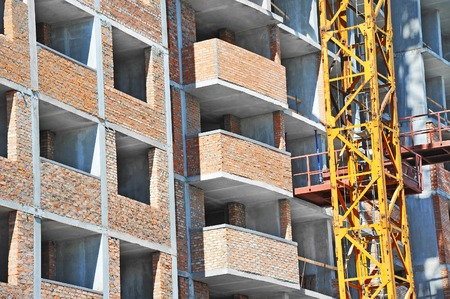 realestate: Crane and building from concrete and brick