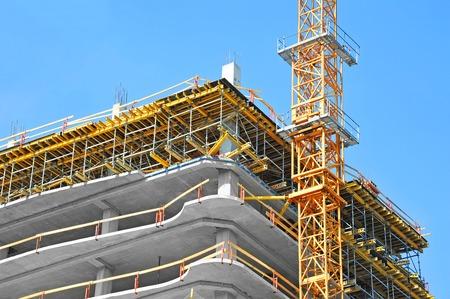 Kraan en gebouw in aanbouw tegen de blauwe hemel Stockfoto - 79560057