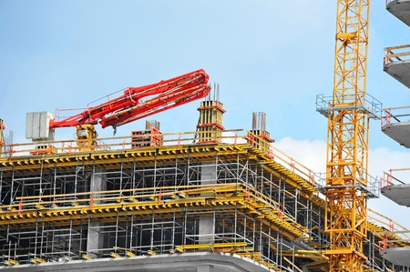 realestate: Crane and building under construction against blue sky Stock Photo
