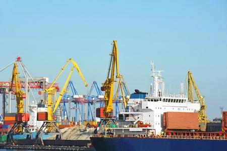 Bulk cargo ship under port crane bridge Stock Photo