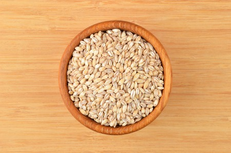 Barley grits in bowl on wooden background Stock Photo