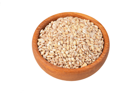 Barley grits in bowl, isolated on white background