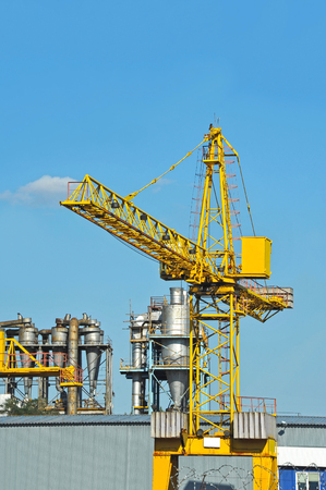 Crane and factory separating chimney over blue sky