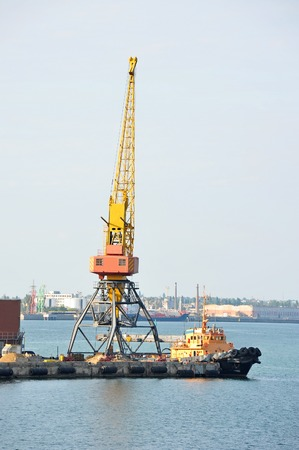 Tugboat and crane in harbor quayside on Odessa, Ukraine Editorial