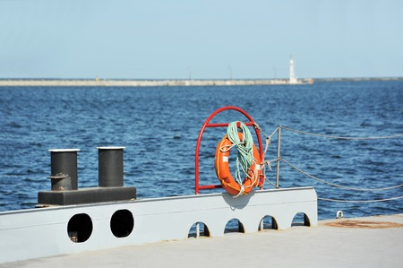 Red lifebuoy and bollard on metal pier
