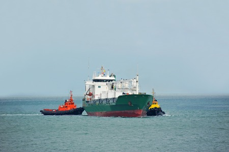Tugboat assisting refrigerated cargo carrier to harbor quayside