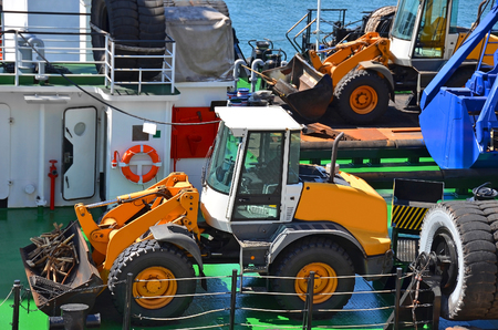 Bulldozer and bucket on floating crane deck Stock Photo