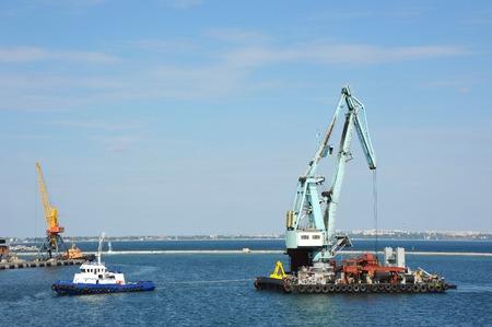 Tugboat assisting floating cargo crane to harbor quayside Stock Photo
