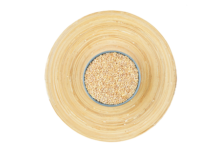 Barley grits in bowl on wooden plate background Stock Photo