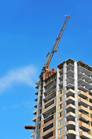 Crane and building under construction against blue sky Stock Photo