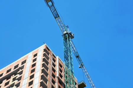 Crane and building under construction against blue sky Banque d'images