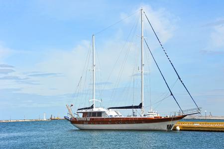 Sailing motor yacht over harbor pier, Odessa, Ukraine