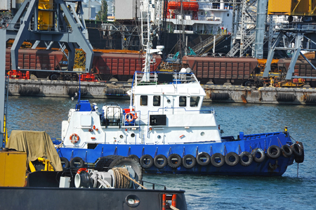 Tugboat and crane in harbor quayside on Odessa, Ukraine Stock Photo