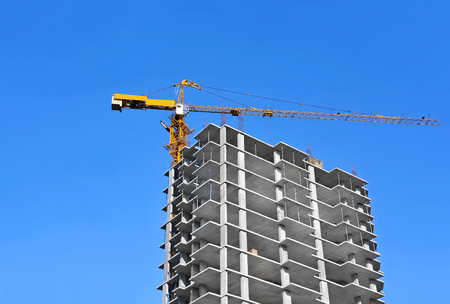 Crane and building under construction against blue sky Imagens