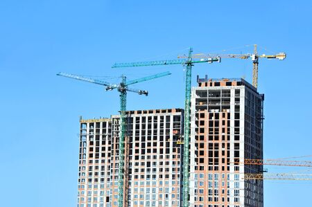 Crane and building under construction against blue sky Stockfoto