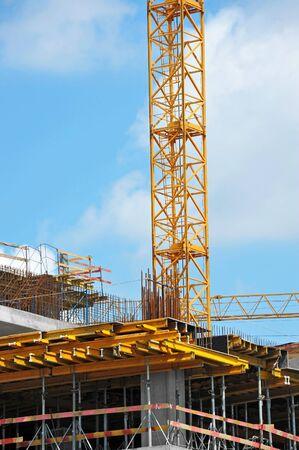 Grúa y edificio en construcción contra el cielo azul