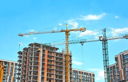 Gru e costruzione in costruzione contro il cielo blu Archivio Fotografico