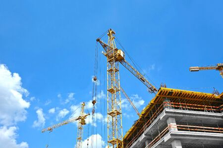 Crane and building under construction against blue sky 写真素材