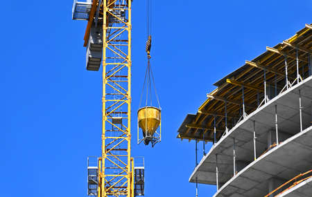 Crane lifting concrete mixer container on construction site