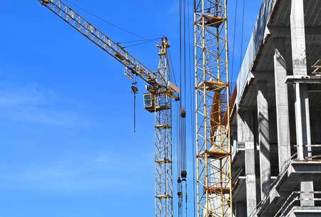 Crane and building under construction against blue sky Foto de archivo