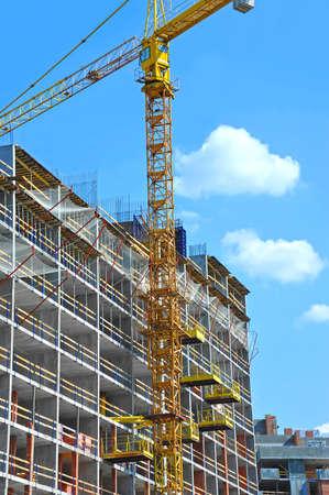 Crane and building under construction against blue sky Standard-Bild