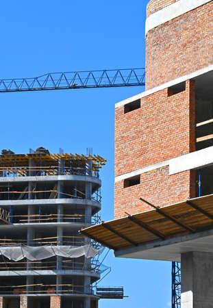 Crane and building under construction against blue sky