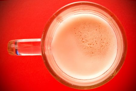 Beer mug seen from the top; isolated on red background. photo