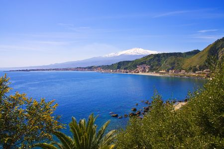 Sicilian seascape from Taormina: mount Etna beyond the blue sea and trees frame on foreground photo