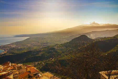 Sicilian seascape, near Taormina: mount Etna beyond the sea; Castelmola village on foreground photo