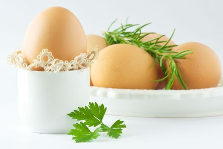 Several eggs in holder with fresh rosemary and a top of parsley on white background photo
