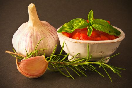 Tomato Sauce in a bowl with a garlic bulb, basil leaf and top of rosemary photo