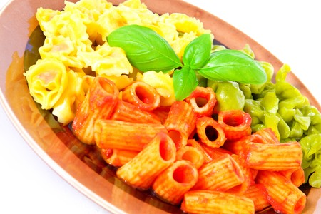 Several kinds of pasta on a plate with a basil leaf on the center; on white background photo