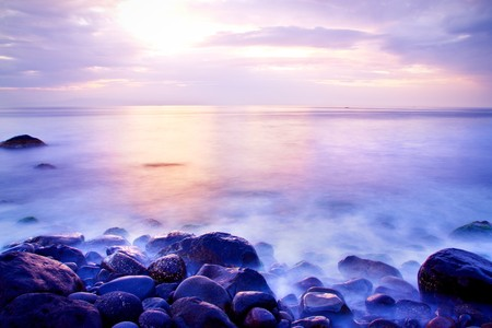 purple sunset: Sea at sunrise with motion waves due to a long exposure; rocks on foreground Stock Photo