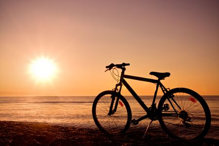 silhouette of a bike on the beach at sunset photo