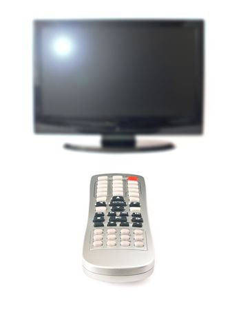 Remote control on foreground and a blurred LCD television on background; isolated on white photo