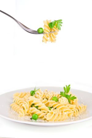 eating pasta: Silver Fork and white plate with fusilli pasta and green peas; isolated on white background with copy space Stock Photo