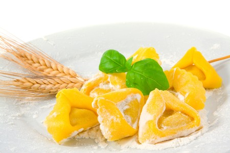 fresh raw tortellini in a plate with ears wheat, flour, and a basil leaf; isolated on white background photo
