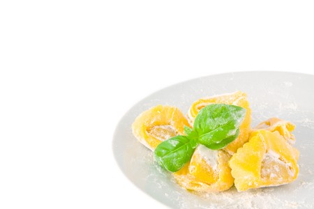 Tortellini pasta with basil on a plate; isolated on white background photo