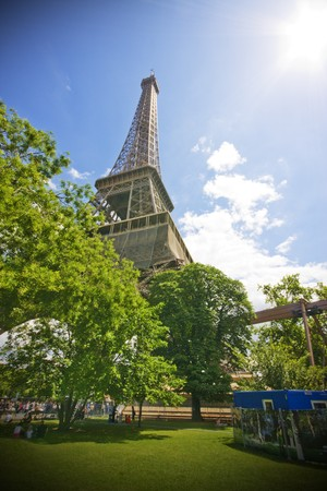 Paris - Eiffel Tower on a blue sky with green trees on foreground; copy space on the right photo