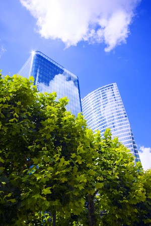 costruction: Modern office buildings on a blue sky with trees on foreground, ecology concept Stock Photo