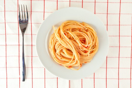 A plate of spaghetti pasta on a checked tablecloth with a silver fork seen from above photo